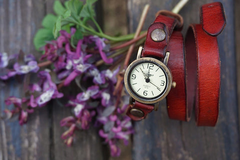 Vintage red watch and purple flowers on the wooden bench