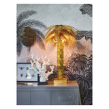 Brass palm tree lamp standing on a cupboard