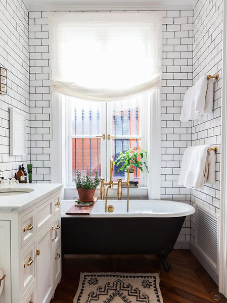 Large white tiles in the bathroom and freestanding black bath tub