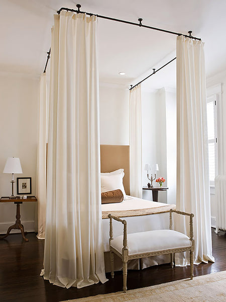 Long white curtained four poster bed frame