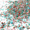 Sprinkle mix: teal, gold, light blue, and pink sprinkles. Shapes are different size spheres and rods. Poured out on a white table.
