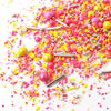 Yellow and two shades of pink sprinkles with gold rods and spheres. Poured out on a white table.