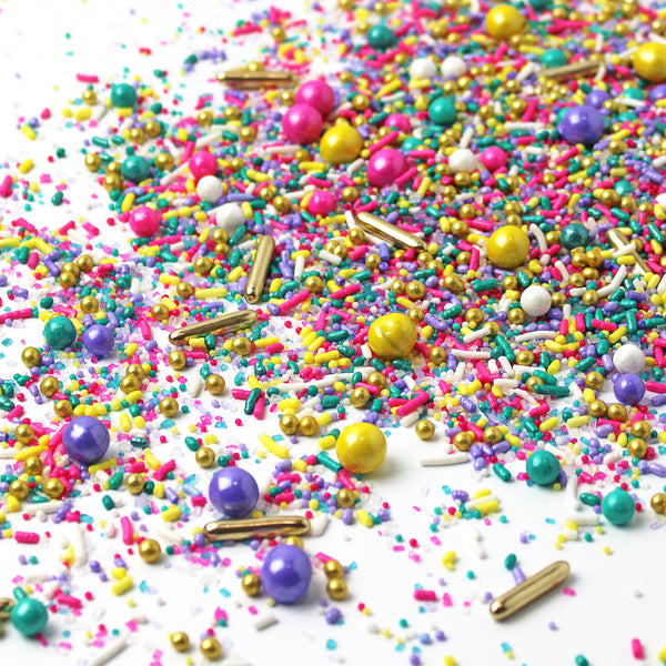 Sprinkle mix: teal, yellow, pink, purple, and white sprinkles. Some shaped as a rod, others as a sphere all poured out on a white table.
