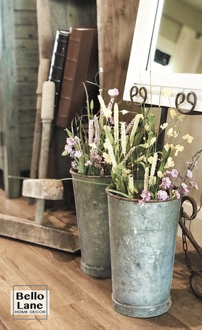 Summer flowers in two galvanized metal vases sitting on a hardwood floor