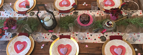 Valentine's Day table set for eight. Gold changes layered with burgundy napkins and whit plates, topped with a red paper heart and a heart shaped purple cookie.