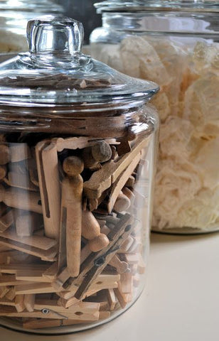 Glass jar filled with wooden clothes pins