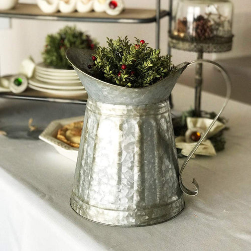 Farmhouse style galvanized milk pitcher with attached scroll handle and oversized lip for easy pouring.
