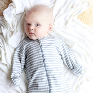 Mokopuna Zip all in one body suit in cloudy bay stripe, being worn by baby