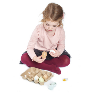 Child playing with Tender Leaf brand, 6 wooden eggs in a cardboard egg box. One cracks open to show the felt egg