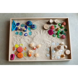 Grapat wooden tray filled with sand and colourful natural toys to invite play