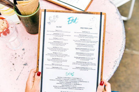 Hands holding a menu at a table