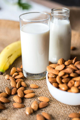 Glass of milk next to a bowl of almonds on a table