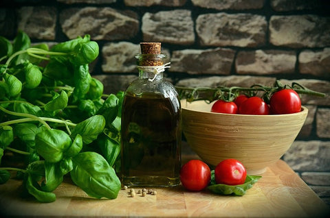 Bottle of olive oil between tomatoes and basil