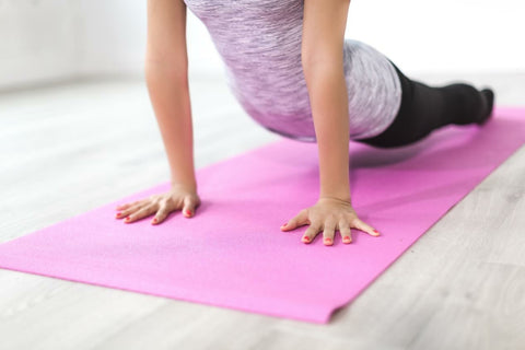 person stretching on a pink mat