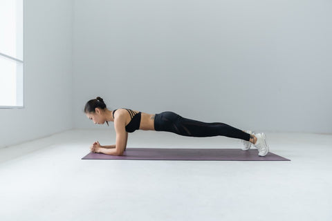 woman in a white room doing a plank