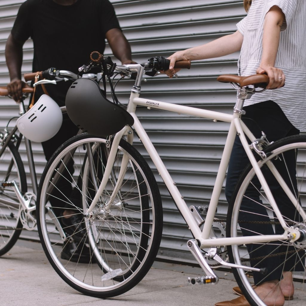 two people standing next to bikes
