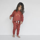 Classic slouch style pant and matching sweater with 'mini' embroidery on front in colour Rust made 100% merino with folded stretchy waistband and natural cotton tie