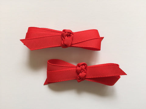 Two hair clips with bright red grosgrain bows