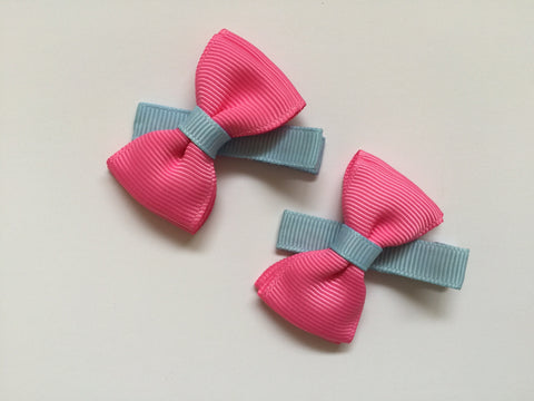 Two hair clips with pink grosgrain bows