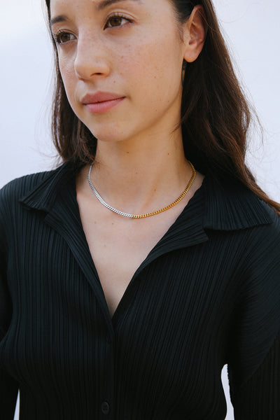 Model wearing two tone gold silver necklace and black top