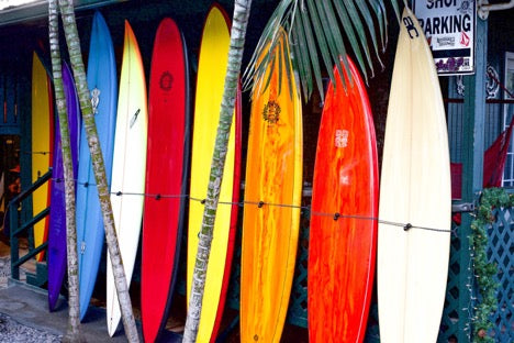colored surfboards lined up on surf shack