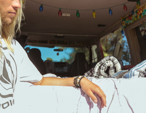 surfer dude wearing mens surf bracelets in hippie van