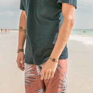 surfer dude at the beach wearing black wave string bracelet