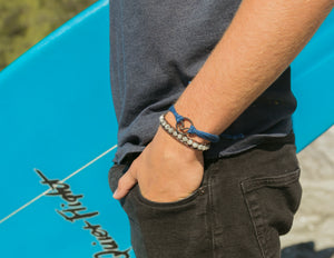 surfer wearing black wave pura vida string bracelet