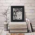 An image of a framed Dictionary Art Print resting on a pile of books.