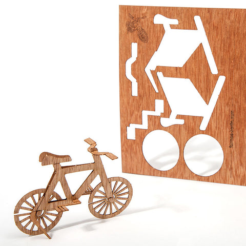 An image of a small wooden bicycle and the wooden postcard it originated from.