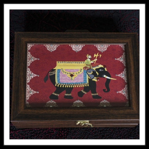 multipurpose box with black elephant print on red background with mahout.