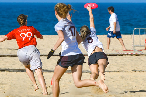 an image of girls playing frisbee at the beach