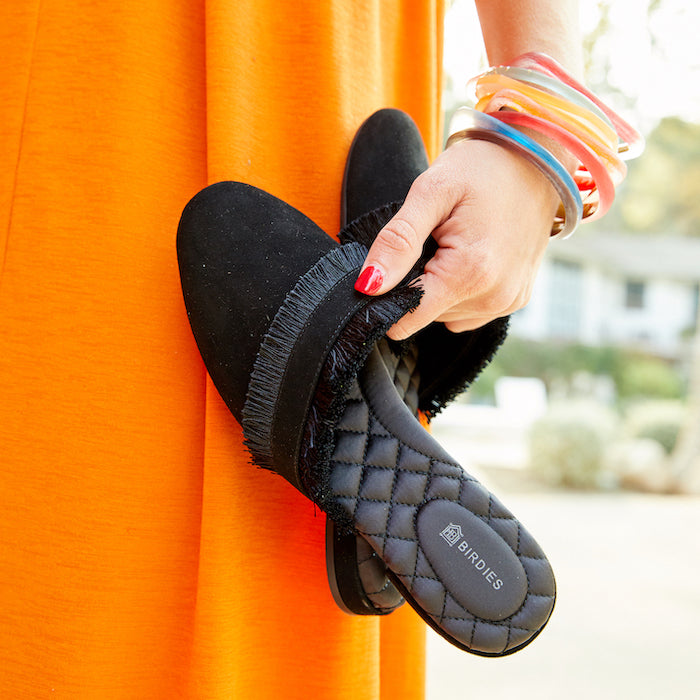 woman in orange dress holding black slides