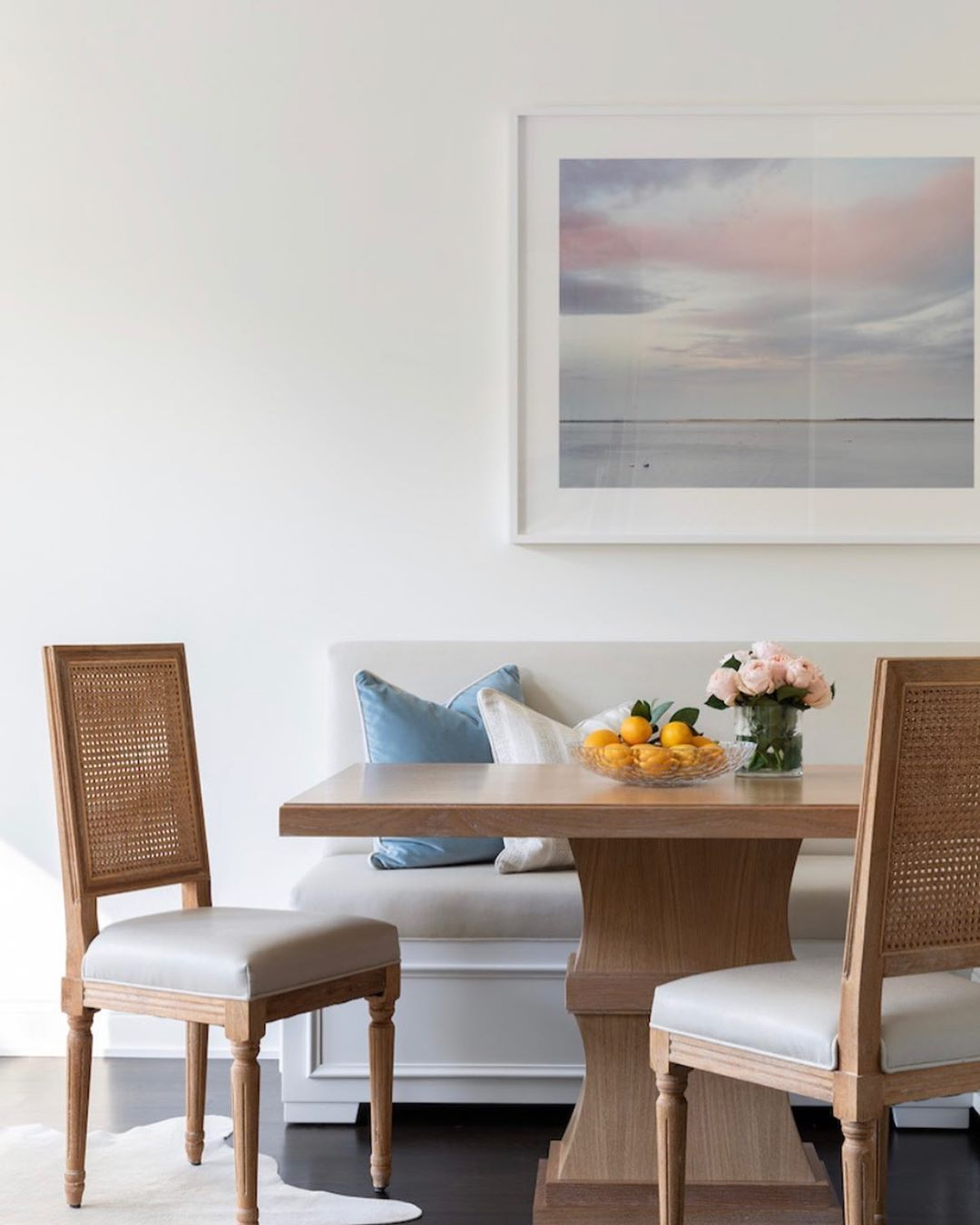 Kitchen nook with beautiful painting, bench, chairs, and table with fresh flowers and citrus