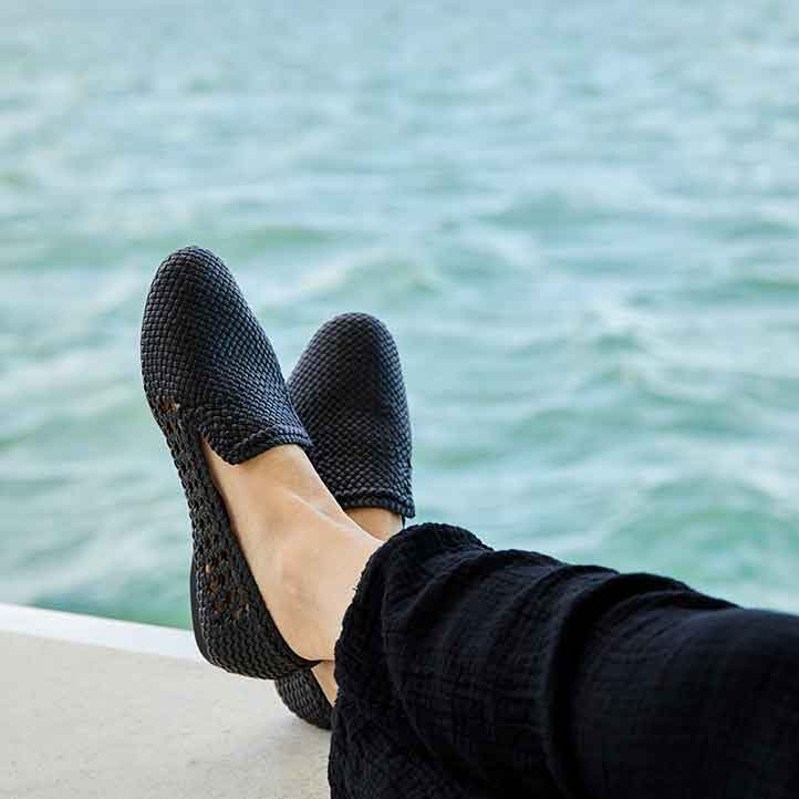Woman wearing black woven flats with feet up against ocean background