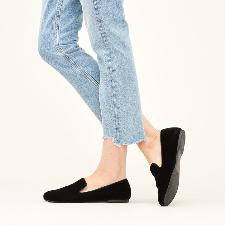 Woman wearing black velvet Starling flats with raw-edge jeans