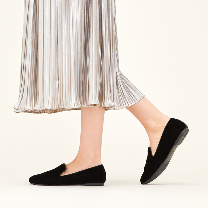 Girl wearing a pleated metallic skirt and showing off her Birdies Starling black flats