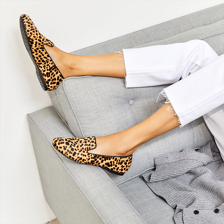 Woman with white jeans on a gray couch wearing Birdies cheetah Starling flats