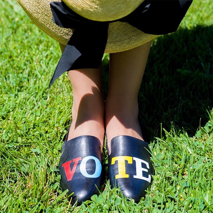 """close-up of woman wearing black leather """"vote"""" flats"""