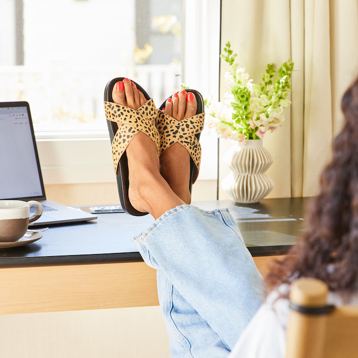 woman wearing cheetah-print crossover sandals with jeans