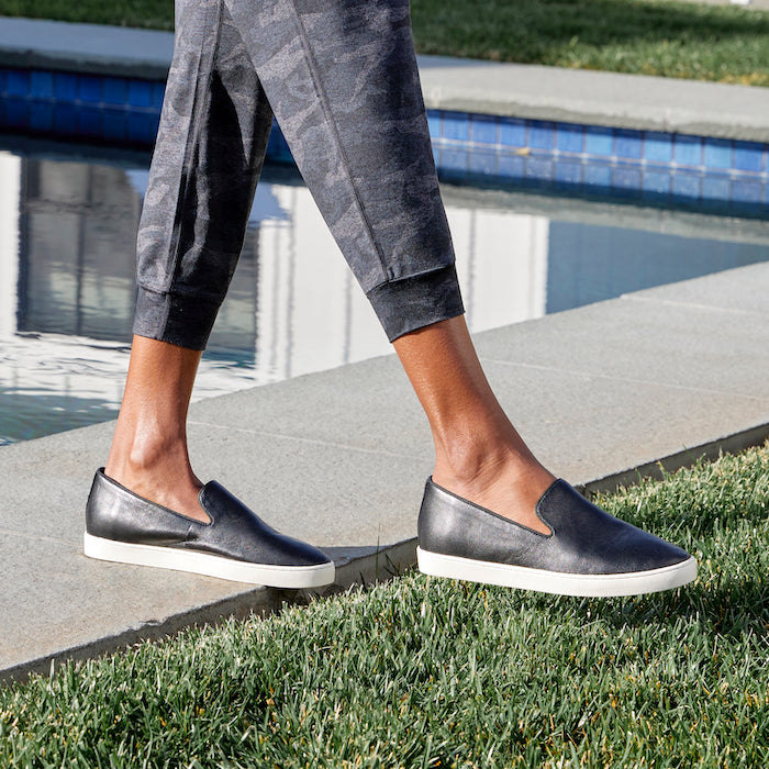 woman wearing black leather slip-on sneakers with camo joggers