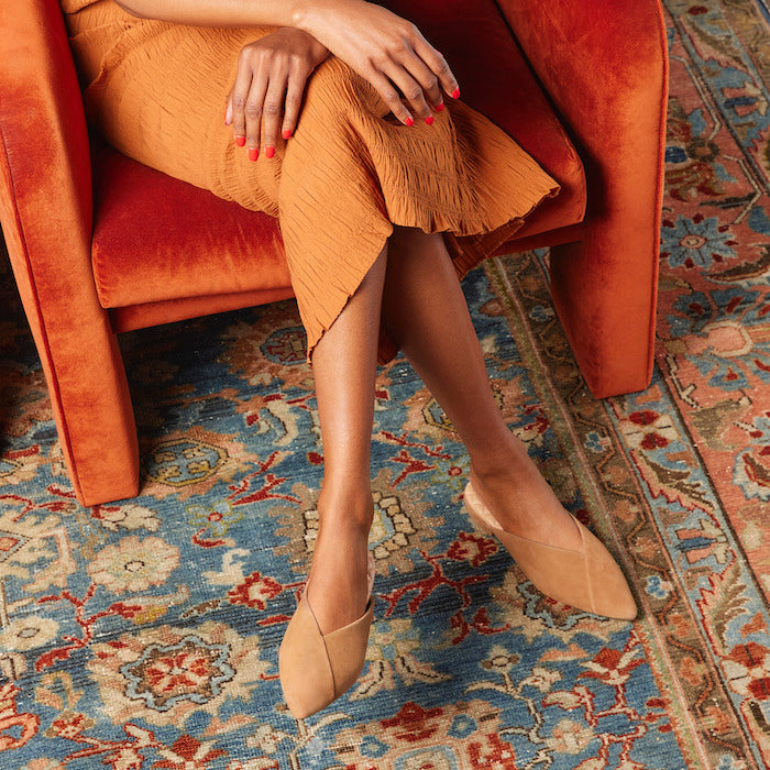 woman wearing tan suede slides with brown textured dress