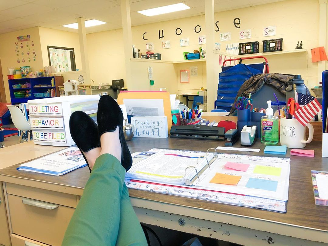 teacher wearing black velvet flats with feet up on desk