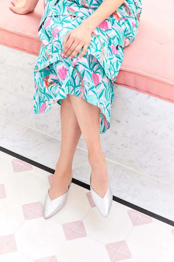 woman wearing silver slides and floral dress