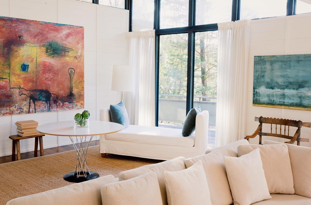 Light-filled living room with cream couches and large, abstract artwork on walls