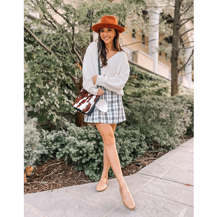 woman wearing plaid skirt, sweater, beige leather flats