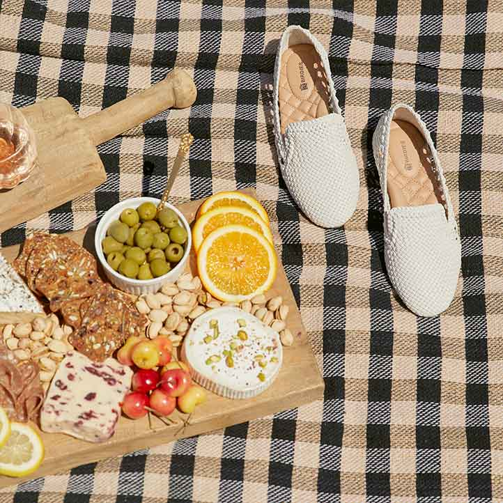 silver woven flats on picnic blanket with rosé and charcuterie board