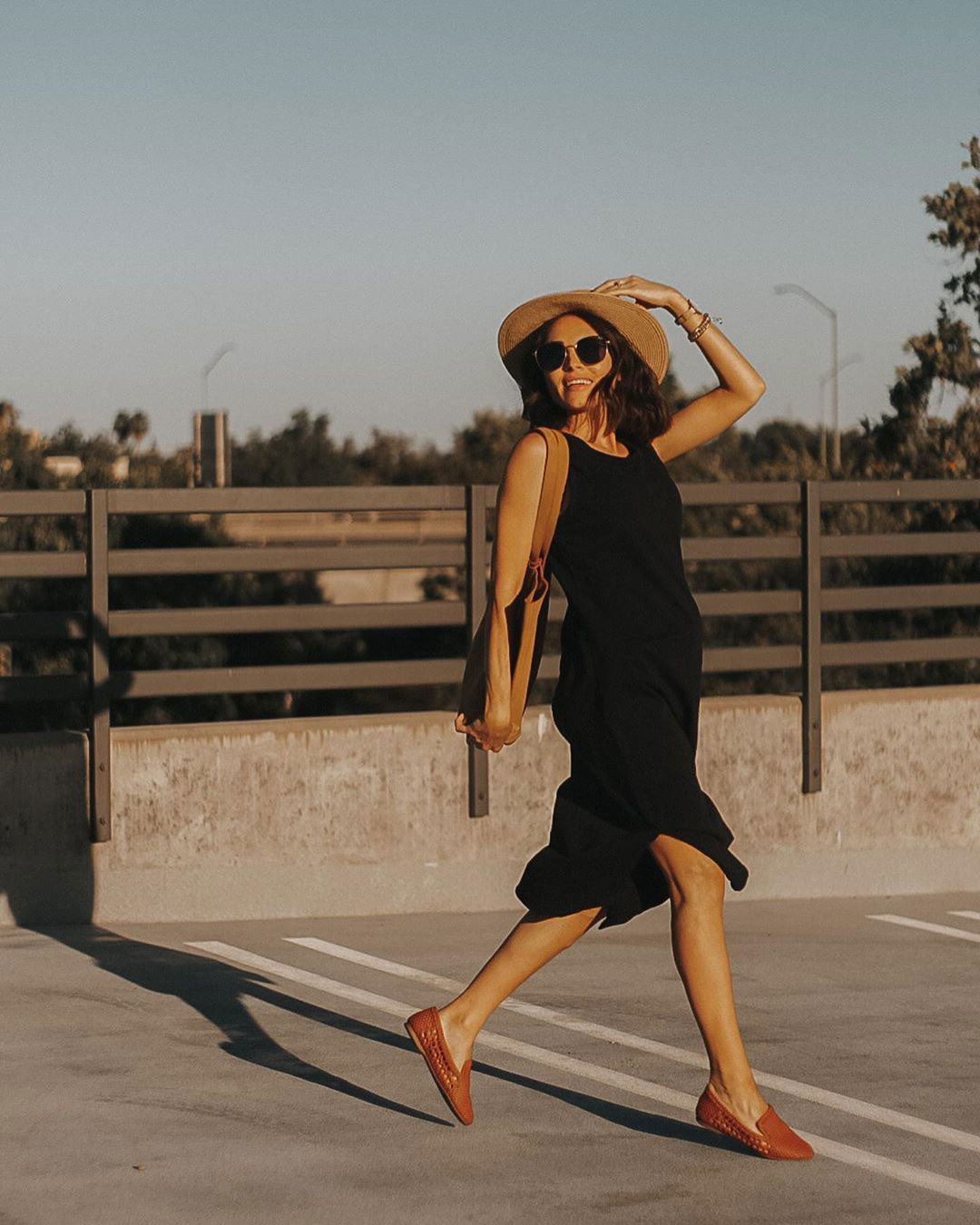 woman walking in brown woven flats and simple black dress