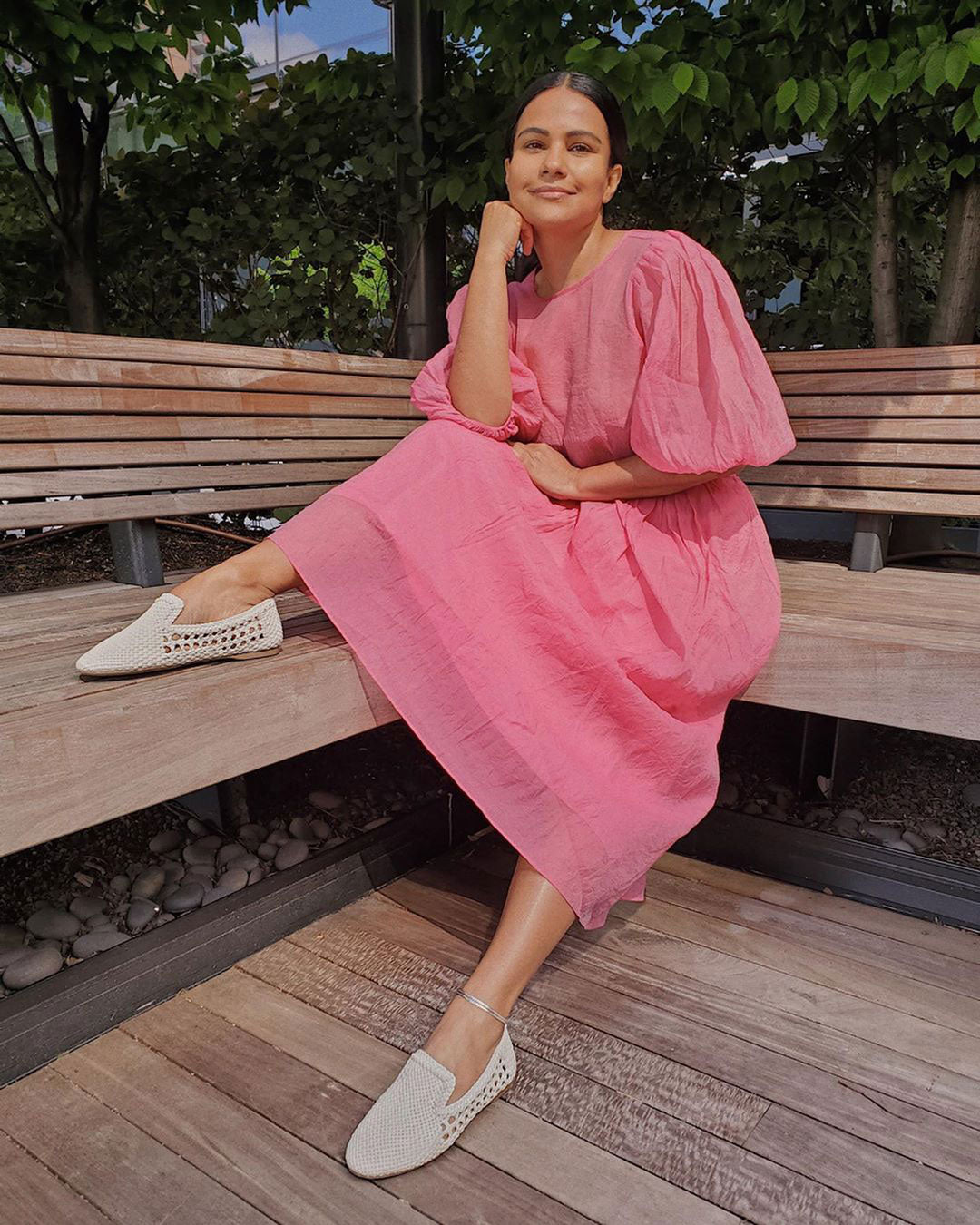 woman sitting on patio wearing white woven flats with bright pink dress