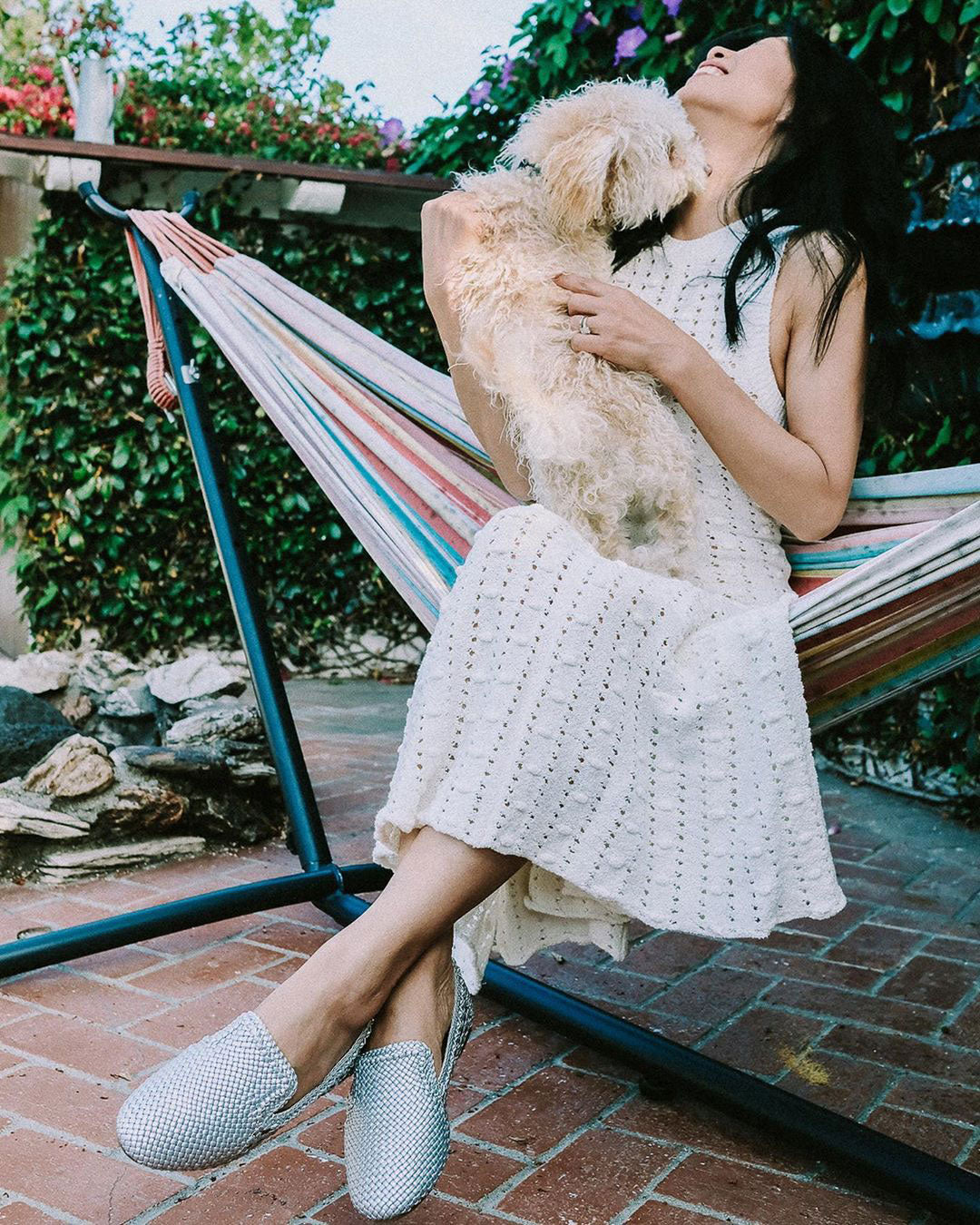 woman on hammock with dog wearing silver woven flats and long knit dress